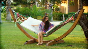 Inhammock relaxado e balançando da mulher moreno de sorriso nova na praia tropical video estoque