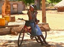 Inharrime, Мозамбик - 10-ое декабря 2008: Неизвестная девушка сидя o Стоковые Изображения