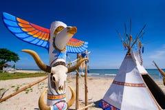 Inheemse Amerikaanse Indische tipi en totempaal op het strand blauwe sk Stock Afbeelding