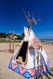 Inheemse Amerikaanse Indische tipi en totempaal op het strand blauwe sk Stock Foto