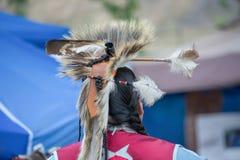 Inheemse Amerikaanse mens die traditionele plechtige kleding en hoofdkleding dragen Stock Foto