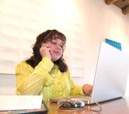 Inheemse Amerikaanse vrouw op een celtelefoon in bureau Stock Foto's