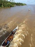 Inheemse Mensen met traditionele houten canoo: De Rivier van Amazonië: Brazilië stock fotografie