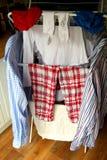 Inhemsk tvätteri, skjortor, pyjamas, sockor som torkar på en airer royaltyfria foton
