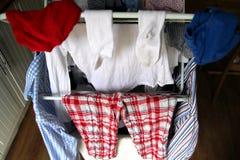 Inhemsk tvätteri, skjortor, pyjamas, sockor som torkar på en airer royaltyfri foto