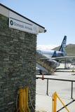 Inhemska ankomster undertecknar med den Air New Zealand nivån, den Queenstown flygplatsen med berg i bakgrund arkivbild