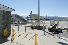 Inhemska ankomster undertecknar med den Air New Zealand nivån, den Queenstown flygplatsen med berg i bakgrund royaltyfri fotografi