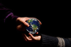 Inheritance of the planet. An hand of an adult give the world to a child Stock Photo