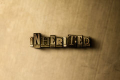 INHERITED - close-up of grungy vintage typeset word on metal backdrop Stock Images
