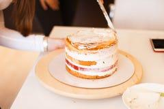 Inhysa det bärande förklädet för frun som gör fulländande handlag på kakan för födelsedagefterrättchoklad Kvinna som gör den heml Royaltyfria Foton