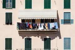 Inhysa fasaden med kläder som ut hänger för att torka Italiensk kultur royaltyfri fotografi