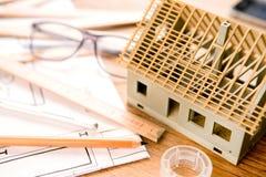 Inhysa miniatyren under konstruktion på ett arkitektskrivbord royaltyfri foto