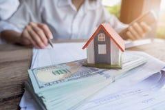 Inhysa modellen och pengar i hand, begrepp av fastigheten och avtal royaltyfri foto