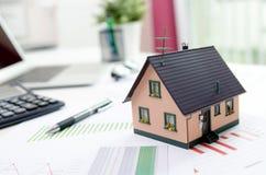 Inhysa modellen på skrivbordet, inteckna eller begrepp för husbyggnad Arkivbild