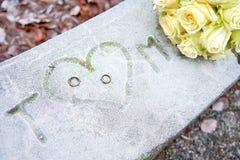 Iniciales, anillos de bodas y rosas blancas en una superficie congelada imágenes de archivo libres de regalías