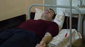 Iniezione endovenosa Infusione della droga in una vena con un IV Un uomo in un reparto di ospedale sta trovandosi su un letto E video d archivio