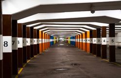 Inifnite underground car park with numbered and colourful pillars stock image