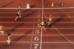 inish löparegruppkvinnor sprintar loppet på stadion Arkivfoton
