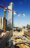 Downtown Construction Site. The initial stage of foundations in a construction site of a future skyscraper, with a tall derrick crane and skyscraper rising high Stock Image