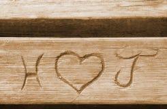 Initialen einer Liebe verbinden, geschnitzt in einer Bankplanke Stockfotos