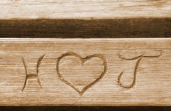 Initials of a love couple, carved in a bench plank.  Stock Photos