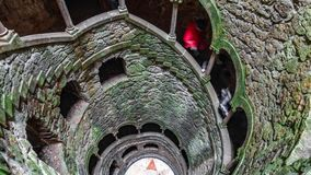 The Initiation Well pattern with blurred tourists descending. Wide angle top view of the Initiation Well with blurred tourists descending floors in Sintra Stock Photo