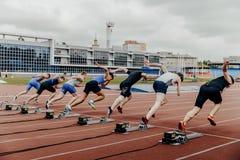 Inizi gli sprinter degli uomini su 100 metri correre Immagine Stock