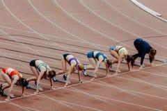 Inizi gli sprinter femminili in 100 metri correre Fotografie Stock Libere da Diritti