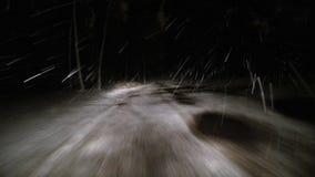 Inizi a guidare attraverso la foresta dell'inverno sulla strada nevosa alla notte stock footage