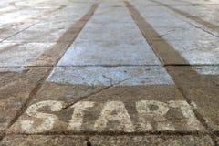 Inizi la parola sulla terra del cemento Fotografia Stock
