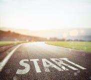 Inizi scritto alla terra su una strada al tramonto Immagini Stock Libere da Diritti