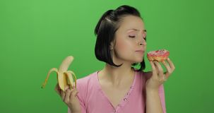 Iniziare cibo sano Dica no ad alimenti industriali Ciambella o banana di scelto da mangiare fotografia stock