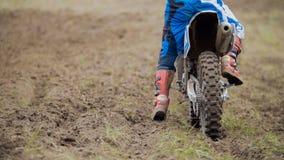 Inizio del corridore di motocross che guida la sua bici del MX dell'incrocio della sporcizia - retrovisione immagine stock