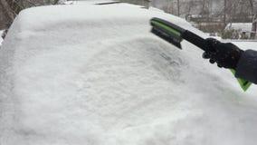 Inizio della donna che rimuove neve dall'automobile innevata archivi video