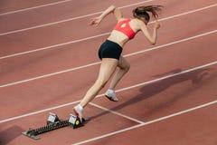 Inizio dello sprinter di Womanl a 400 metri Immagine Stock Libera da Diritti