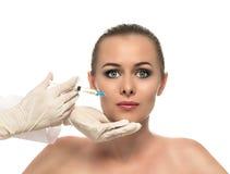 Injeção cosmética às mãos consideravelmente bonitas da cara e do esteticista da mulher com seringa. foto de stock royalty free