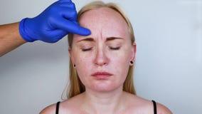 A injeção de Botox na testa, remove o enrugamento vertical Jovem mulher na recepção no esteticista, o procedimento de vídeos de arquivo