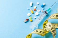 Injeções para a perda da beleza e de peso do corpo Tabuletas, seringa e fita de medição amarela foto de stock