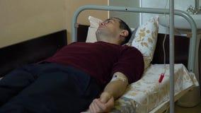 Inje??o intravenosa Infus?o da droga em uma veia com um IV Um homem em uma divis?o de hospital est? encontrando-se em uma cama vídeos de arquivo