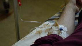 Inje??o intravenosa Infus?o da droga em uma veia com um IV Um homem em uma divis?o de hospital est? encontrando-se em uma cama M? video estoque