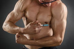 Injecting Steroids. Close up of a muscular man injecting himself with steroids stock photo