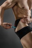 Injecting Steroids. Close up of a muscular man injecting himself with steroids royalty free stock photography