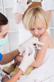 Injection. Nurse giving injection to little girl patient Royalty Free Stock Photo