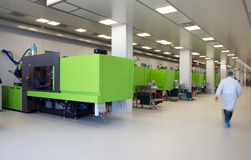 Injection molding of biomedical products in clean room. Injection molding (or moulding) of biomedical products in a large cleanroom. A cleanroom or clean room is royalty free stock photography