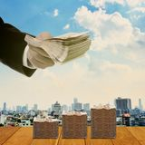 Injection money to economic concept. Hand with money and cityscape background stock images