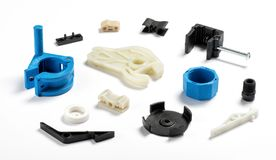 Injection plastic parts. Many different injection plastic parts of white, blue and black colour spread on white background Stock Photography
