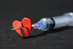 Injection into red heart. With syringe on black background Royalty Free Stock Photography