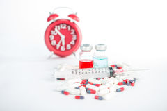 Injection syringe and medicine on red clock background Royalty Free Stock Photography