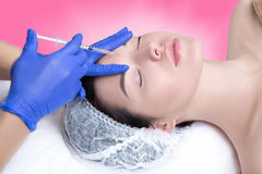 Injections of youth, hyaluronic acid, botox, anti-wrinkle treatm. Beautiful and well-groomed girl is given injections of youth, wrinkle smoothing, hyaluronic Royalty Free Stock Photo