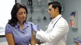 Injektion för doktor Giving Female Patient arkivfilmer